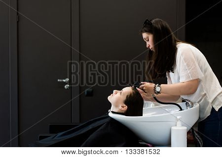 Woman at the hairdresser getting her hair washed and rinsed feeling visibly well.