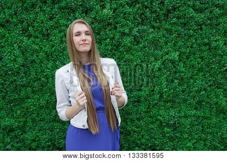 Modest young girl on the green background of leaves