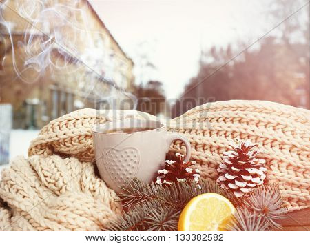 Beautiful winter composition with cup of hot drink on windowsill against snow landscape from outside.