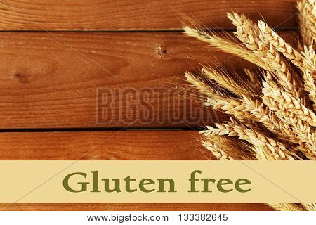 Spikelets of wheat and text Gluten free on wooden background