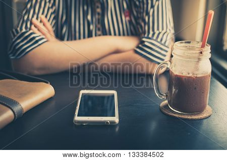 Afternoon scene of young woman sitting in front of her smartphone that put down on table in cafe on weekend. Soft focus on phone screen with vintage filter effect