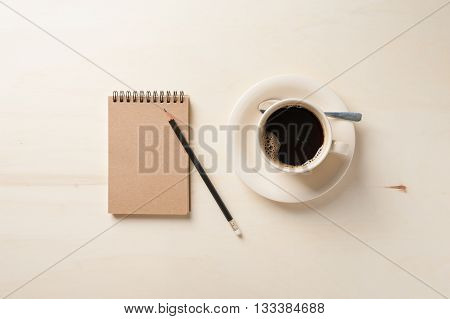 Small notebook with blank area for text or message on brown cover and coffee cup on wood table in morning time