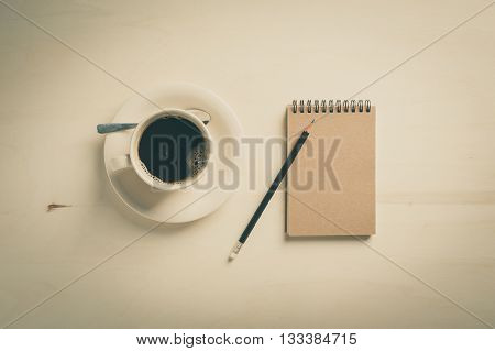 Small notebook with blank area for text or message on brown cover and coffee cup on wood table in morning time with vintage filter effect