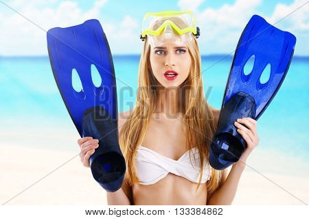 Young beautiful woman in swimsuit with diving mask and flippers on blurred sea background