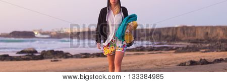 Casualy dressed active sporty blonde woman walking on sandy surfers Cotillo beach in sunset.