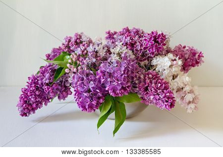 Beautiful bouquet of colored lilac on the table. Vase with beautiful varietal lilacs.