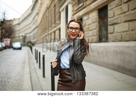 Businesswoman walking down the street while talking on smart phone. Happy smiling caucasian business woman busy