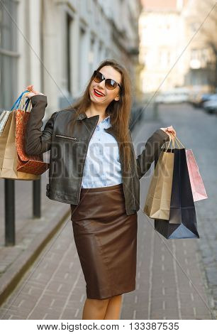 Sale shopping tourism and happy people concept - beautiful woman with shopping bags in the ctiy