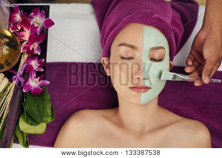Cosmetologist applying clay mask to the face of female client