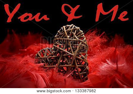 wooden heart in the midst of red feathers on a black background and you & me written
