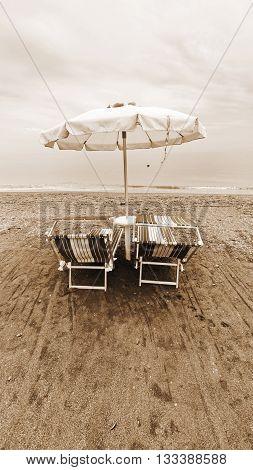 Beach Umbrella and Sun Bed in the Sandy Coast near the Italian City of Minori Vintage Style Sepia