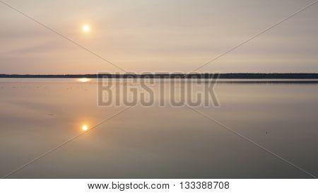 Calm waters on a lake in Saskatchewan Canada as the sun rises