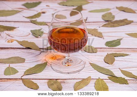 Cognac glass on the red new wooden table with leaves - close up photo