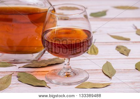 Cognac bottle and glass on the new wooden table with leaves - close up photo