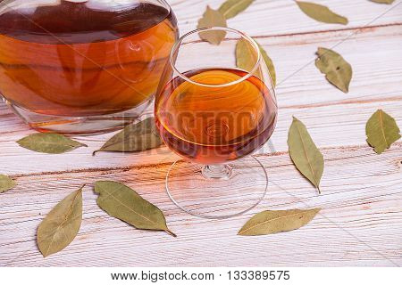 Cognac bottle and glass on the wooden table with leaves - close up photo