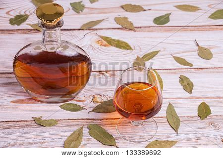 Cognac bottle and glass on the wooden table with leaves - top view
