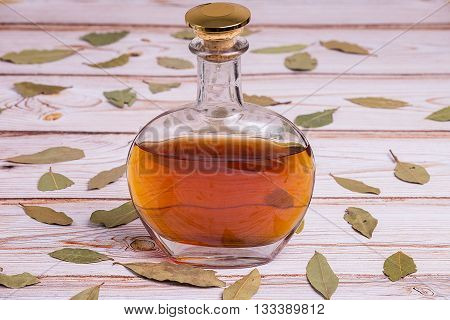 Cognac bottle the wooden table with leaves - close up photo