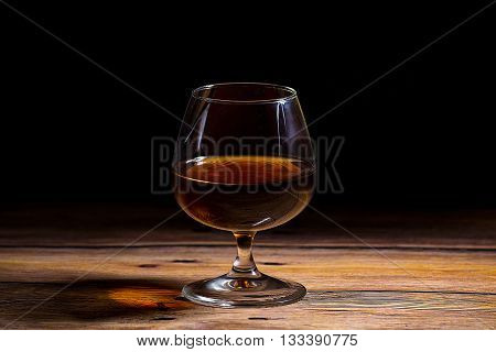 Cognac glass at the wooden table on the black background - close up photo