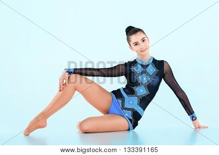 The girl doing gymnastics dance on blue background