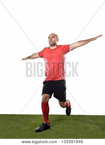 young happy and excited football player in red jersey running on grass pitch and celebrating scoring goal doing flying airplane arms sign isolated on white background