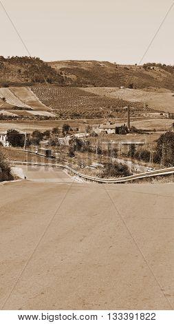 Winding Asphalt Road between Fields of Sicily Vintage Style Sepia