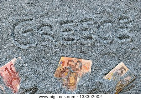 Greece written on the blue sand with money
