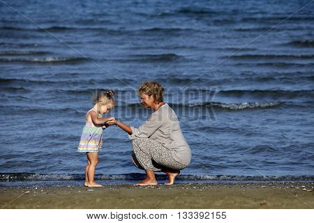 Grandmother with a little granddaughter on the beach
