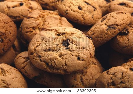 Lots of cookies and biscuits background. Sweet chocolate chips biscuits and cookies texture background. Oatmeal, chocolated drops. Dessert, sweets for tea. Fattening sweets concept