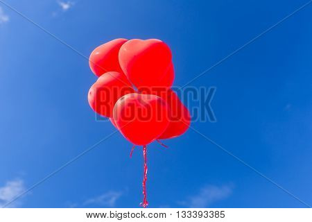 Red heart shaped helium balloons flying in the sky