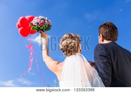 Bride and groom at wedding with helium balloons