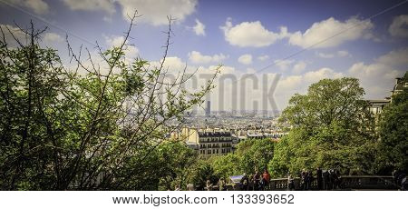 PARIS, FRANCE - MAY 17, 2016: Tourists gather to absorb the beautiful skyline of Paris from this high vantage point in Montmartre, Paris.