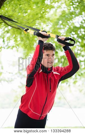 Man doing fitness sling training outdoors