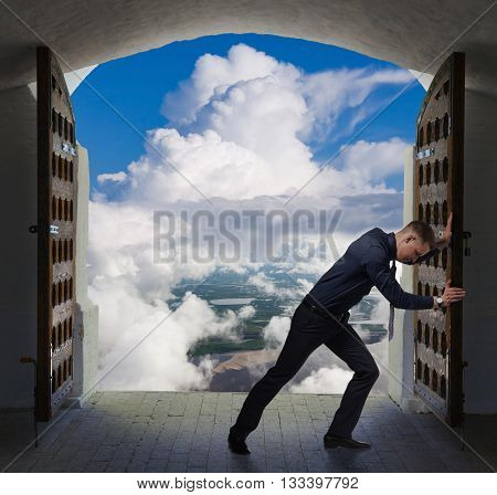 Young businessman is opening a gate to the heavens.