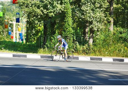 Cycling training on the sunny road. Sport bicycle. Woman cycling on countryside summer road or highway. Training for triathlon or cycling competition. Highway cycling