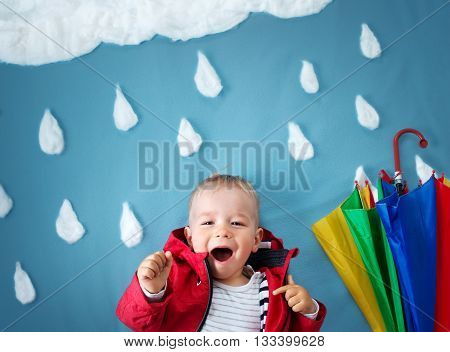 Little boy on blue background in coat with drop shapes and cloud