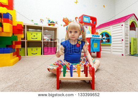 Very Serious Little Girl Playing With Wooden Hammer In Kindergarten