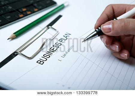 man holding a pen and filling business plan close up