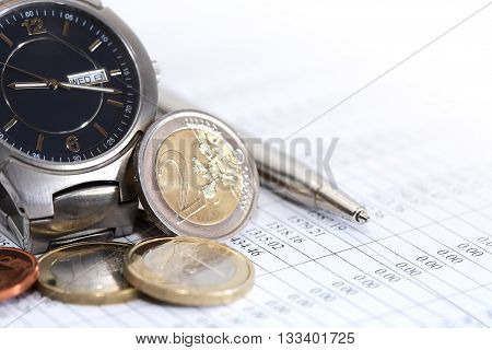 Set of European coins near wristwatch and pen on paper with digits