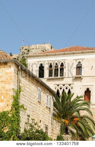 Old buildings with fort in background in Hvar town, Hvar Island, Croatia