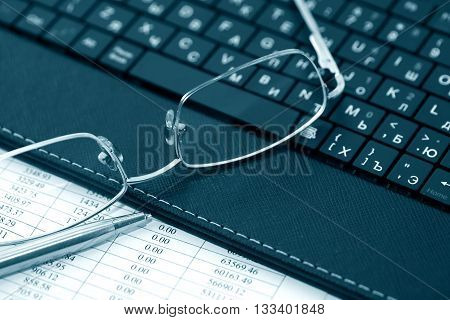 Business concept. Closeup of spectacles on black laptop keyboard