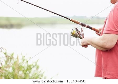 Close-up shot of middle aged man hand holding rod and spinning reel on summer lake - fishing concept