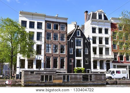 Amstel river, canal of Amsterdam with old houses and wooden houseboat. Fresh green trees and blue sky. Amsterdam in summer.