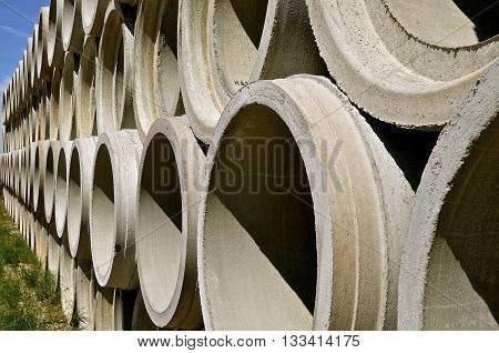 Piles of huge concrete tubes are stacked for engineering industrial projects where water is needed to drain