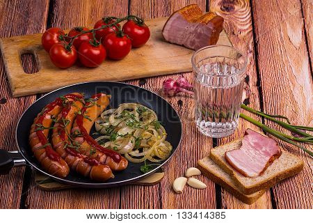 Traditional russian faceted glass of vodka on the old wooden table with snack - fried sausages pork meat garlic and chery tomatoes