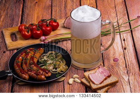 Glass mug with unfiltered white beer with fried sausages tomatoes chery bread garlic and pork meat on the old wooden table