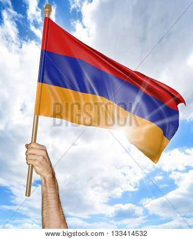 Person's hand holding the Armenian national flag and waving it in the sky, 3D rendering