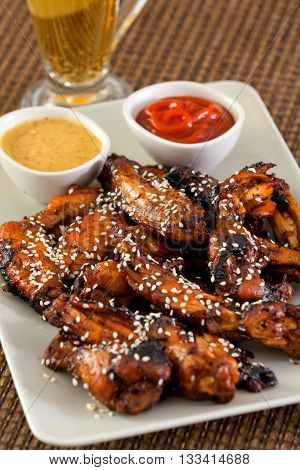 Baked chicken wings with barbecue sauce sesame seeds mustard and catchup. Vertical shot with beer on background
