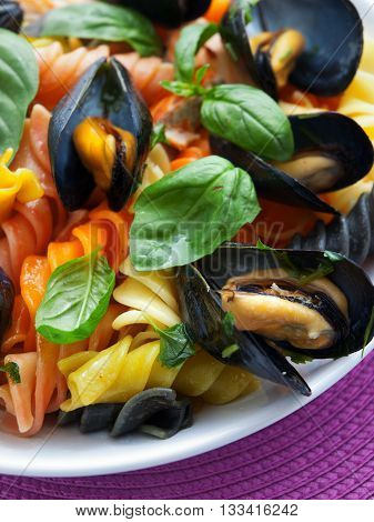 Colorful fusilli pasta with clams and basil