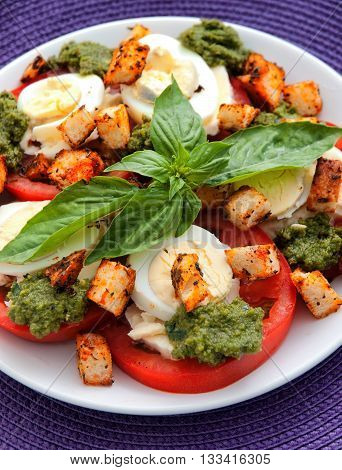 Healthy salad with tomatoes boiled eggs pesto and croutons. Vertical shot