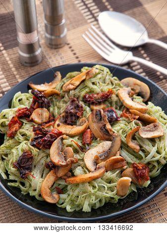 Italian Linguini pasta with pesto and mushrooms in a dark plate. Vertical shot